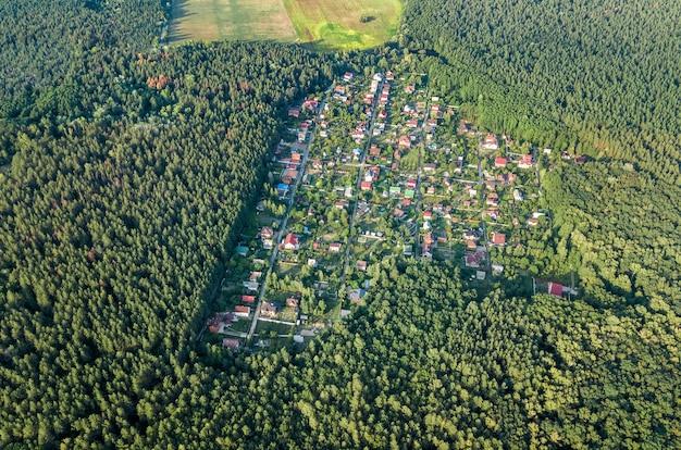 上からの森、田舎の不動産、ウクライナの小さなダーチャ村の住宅地の夏の家の空中のトップビュー