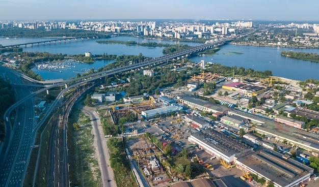 上から工業団地ゾーン、工場の煙突および倉庫、キエフの工業地区の空中のトップビュー