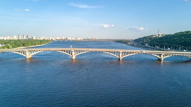 電車とドニエプルの地下鉄鉄道橋の空中ドローンビュー。ウクライナキエフ市のスカイライン
