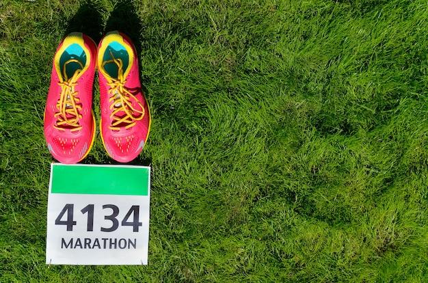 ランニングシューズと草の上のマラソンレースよだれかけ。フィットネスと健康的なライフスタイルのコンセプト