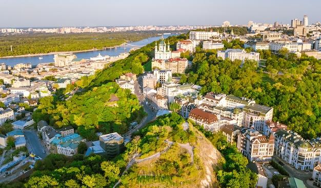 聖アンドリュー教会と上からアンドレエフスカ通りの空中ドローンビュー、キエフ市ポドル地区の町並み