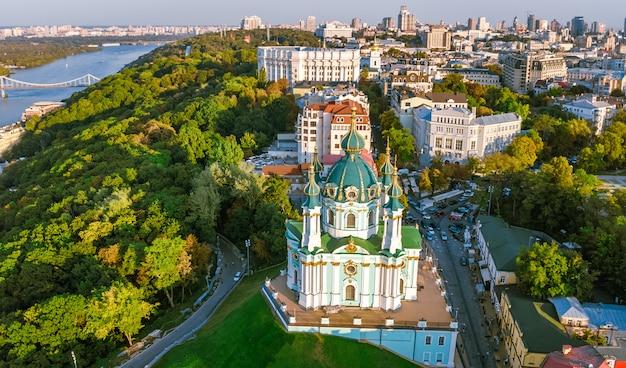 聖アンドリュー教会とアンドレエフスカ通りの空中ドローンビュー。キエフ市ポドル地区の町並み