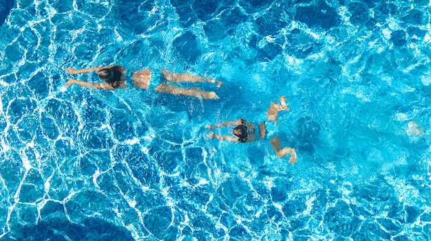 スイミングプールの水空中ドローンビューでアクティブな女の子