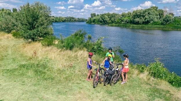 Семья на велосипедах на улице, активные родители и дети на велосипедах