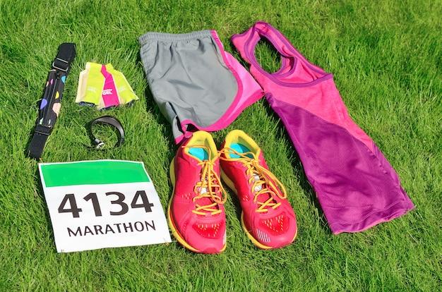ランニングシューズ、マラソンレースビブ、ランナーギア、芝生の上のエネルギージェル。フィットネスと健康的なライフスタイルのコンセプト