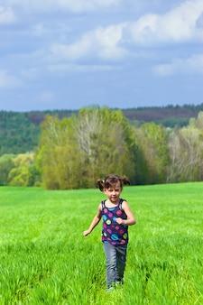 緑の野原で屋外を走っている少女