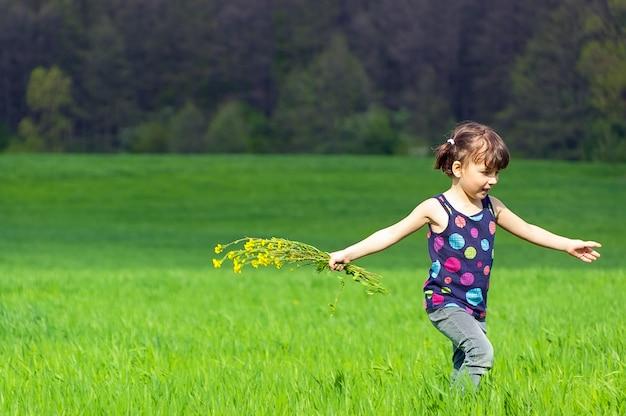 緑の野原に花を持つ少女