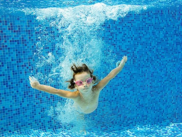 女の子がジャンプして水中プールで泳ぐ