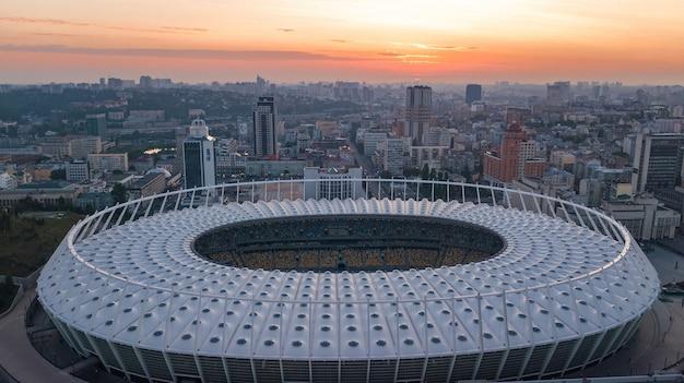 日没のスタジアムとキエフの街並みの空撮