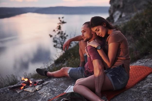 川や湖の海岸を眺めながら山の頂上にある火の近くに座っているバックパックとカップルを抱き締めます。自由とアクティブなライフスタイルのコンセプト