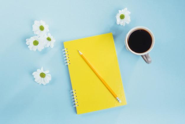 青いノート鉛筆、定規と白い花に