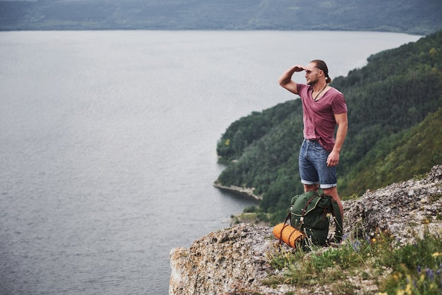 水面上の景色を楽しみながら山の頂上に座っているバックパックを持つ旅行者。自由とアクティブなライフスタイルのコンセプト