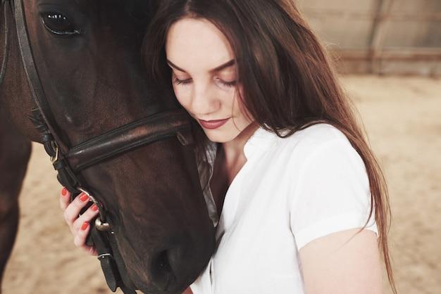 Счастливая женщина общается со своей любимой лошадью. женщина любит животных и катается на лошадях
