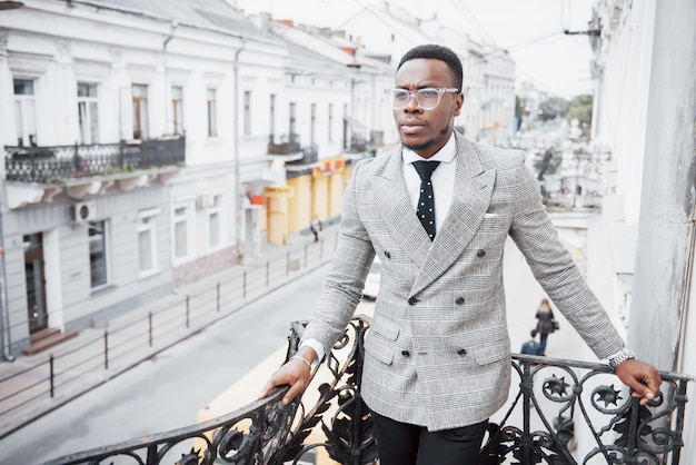 Уверенный черный деловой человек в стильном костюме, стоя на офисном блоке с серьезным выражением лица