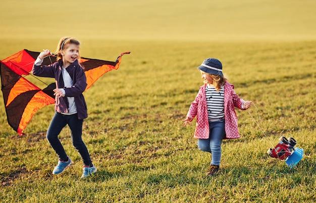 Две маленькие подружки веселятся вместе с кайтом и игрушечной машиной на поле в солнечный день