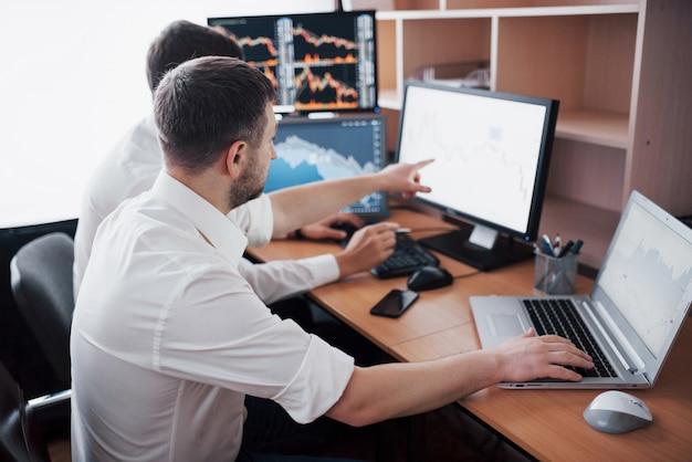 Команда биржевых маклеров разговаривает в темном офисе с экранами. анализ данных, графиков и отчетов для инвестиционных целей. креативная работа трейдеров