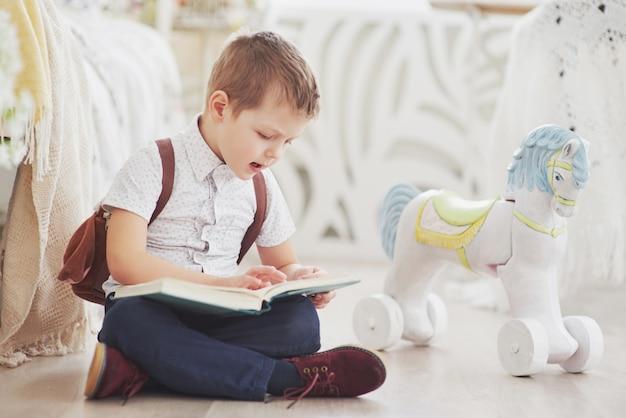 Милый маленький мальчик идет в школу впервые. ребенок с сумкой и книгой. малыш делает портфель, детская комната на заднем плане