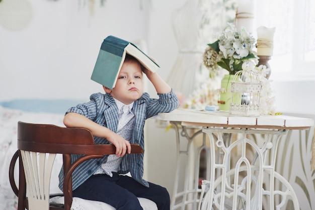 宿題をしている彼の頭の上の本を持つ勤勉な少年の写真