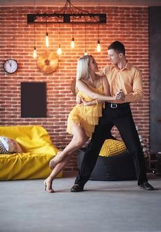 Молодая пара танцует латинскую музыку: бачата, меренге, сальса. две элегантные позы на кафе с кирпичными стенами