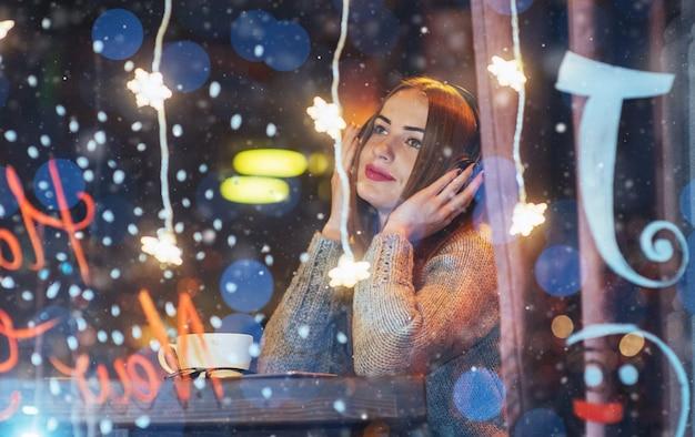 カフェに座って、コーヒーを飲む若い美しい女性。音楽を聴くモデル。クリスマス、新年あけましておめでとうございます、バレンタインデー、冬休み