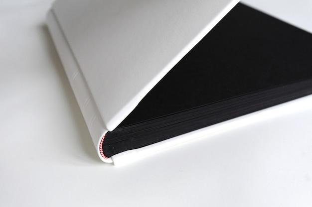 大きな写真集は黒いページと白い木製のテーブルの上に置く