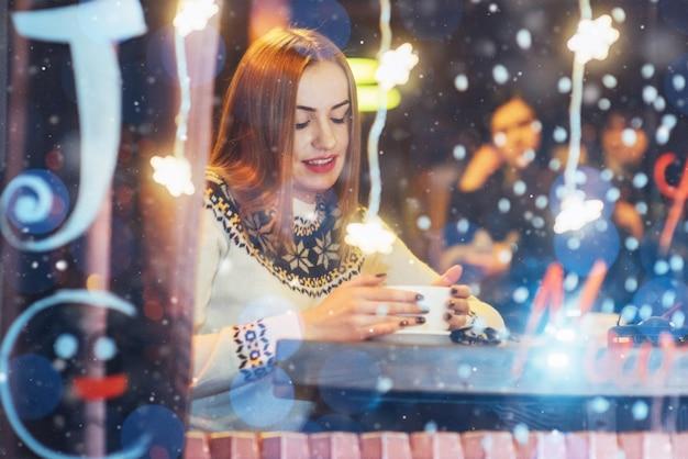 カフェに座って、コーヒーを飲む若い美しい女性。クリスマス、新年あけましておめでとうございます、バレンタインデー、冬休み