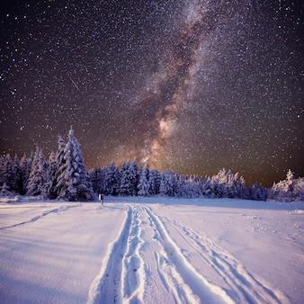 幻想的な冬の流星群と雪をかぶった山々