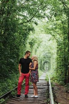 Влюбленная пара в тоннеле зеленых деревьев на железной дороге