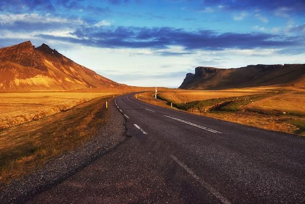 山へのアスファルト道路。ビューティーワールドアイスランド