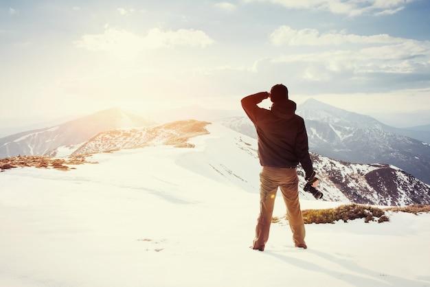 Турист смотрит на пейзаж. фотограф на вершине горы