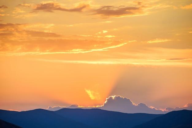 山のシルエットの上の劇的な空