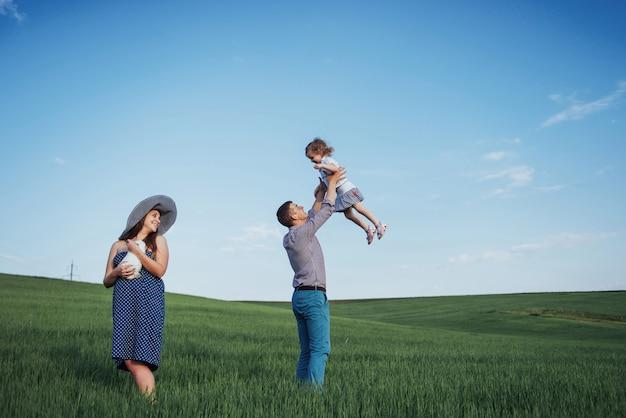 Счастливая семья из трех человек обнимаются на улицах