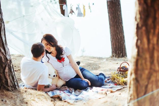 Беременная женщина с мужем на пикнике