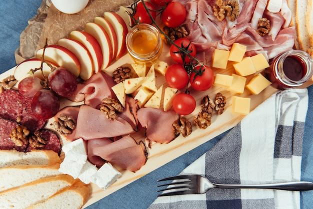 大きな木製のテーブルの肉、パン、野菜