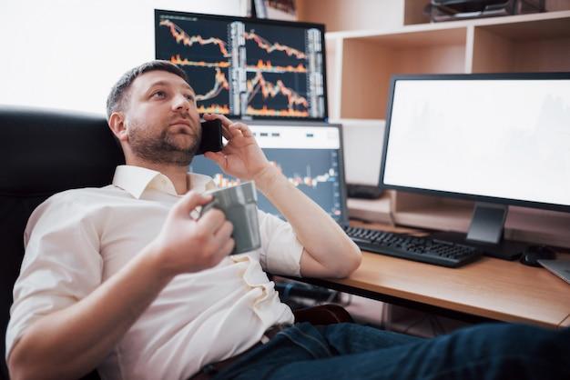 電話で注文を受け付けながら、肩越しにオンラインで取引する株式ブローカー。グラフとデータ分析でいっぱいの複数のコンピューター画面