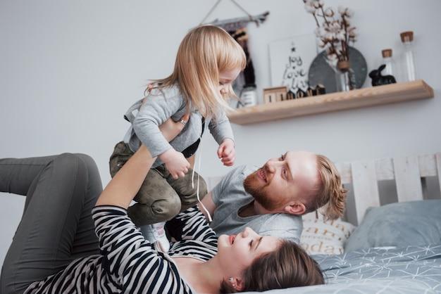 Счастливая семья вместе. мама, папа и дочка обнимаются в спальне в праздничный день
