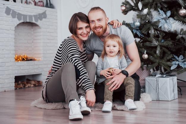 モミの木の近くで一緒に朝のオープニングギフトでクリスマスに幸せな家族