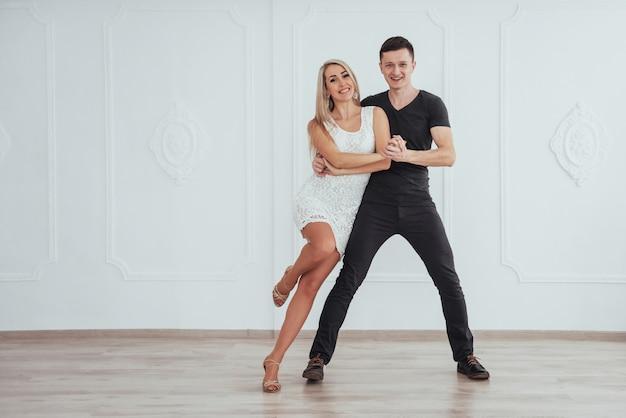 Молодая пара танцует латинскую музыку: бачата, меренге, сальса. две элегантные позы в белой комнате
