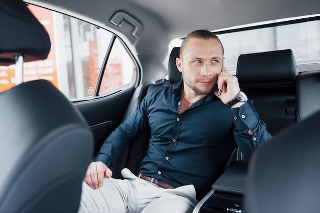現代のビジネスマンが車の後ろで電話で話す