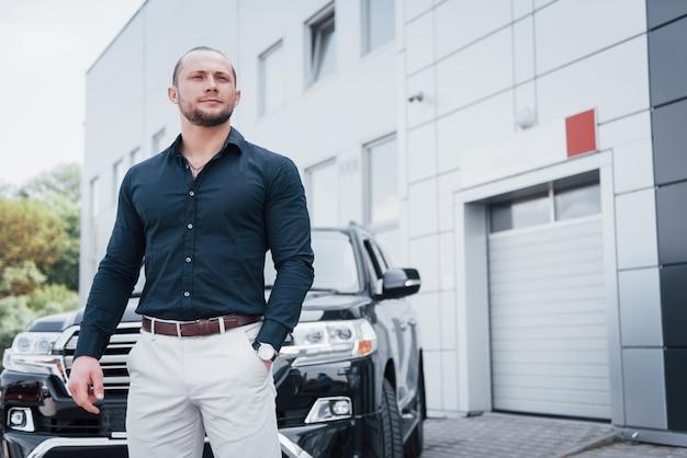 若い堅実なビジネスマンと彼の車がオフィスの近くに