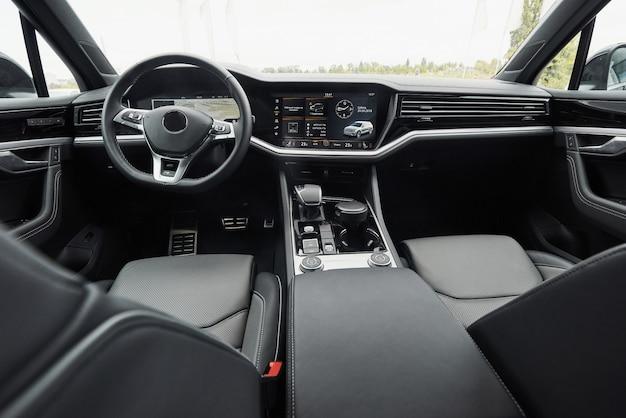 Интерьер престижного современного черного автомобиля. кожаные удобные сиденья и аксессуары и руль