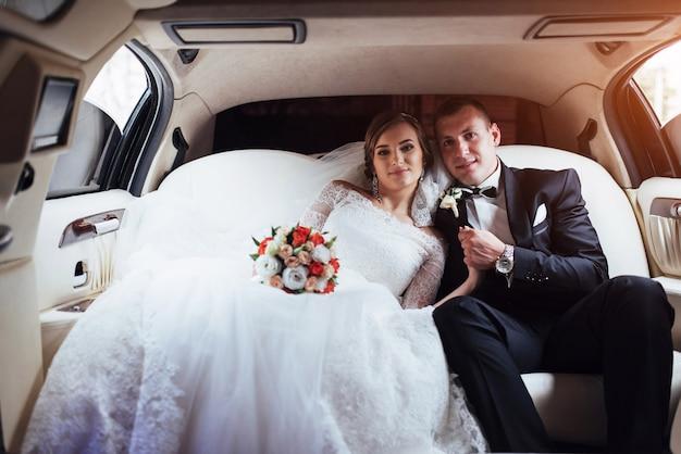 Молодая пара в машине в день свадьбы