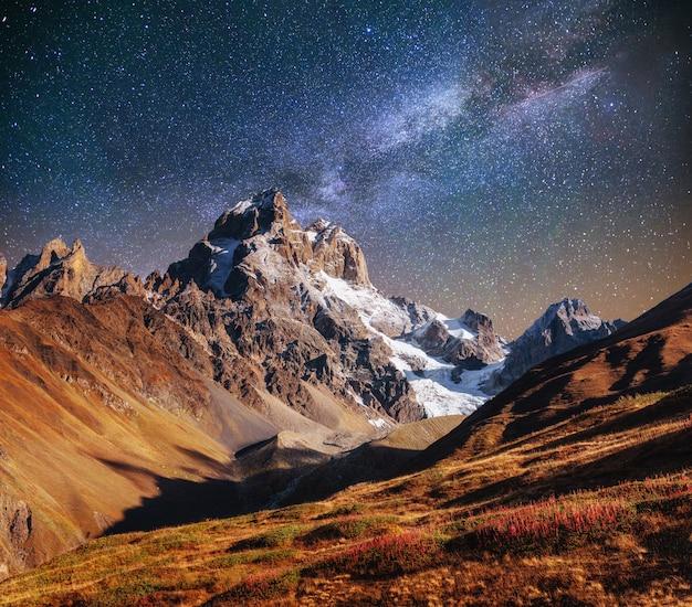 Фантастическое звездное небо. осенний пейзаж и заснеженные вершины. мама