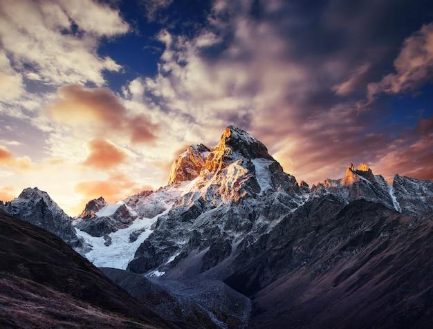 美しい積雲の雲の秋の風景と雪の山。