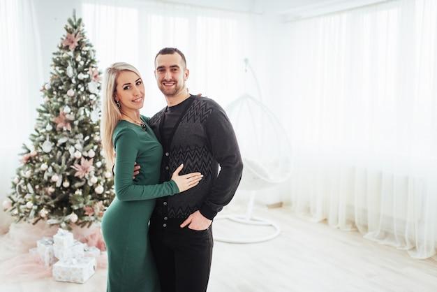 Счастливая молодая пара на рождество, красивые подарки и елка в