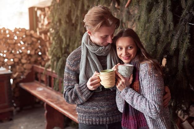 Фото счастливого человека и милой женщины с чашками напольными в зиме. зимний отдых и каникулы. рождественские пара счастливый мужчина и женщина пьют горячее вино. влюбленная пара