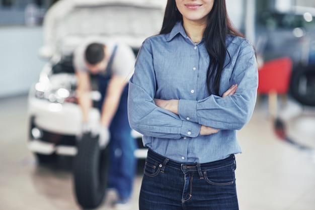 修理ガレージでタイヤタイヤを保持しているメカニック。クライアントの女性は仕事を待つ