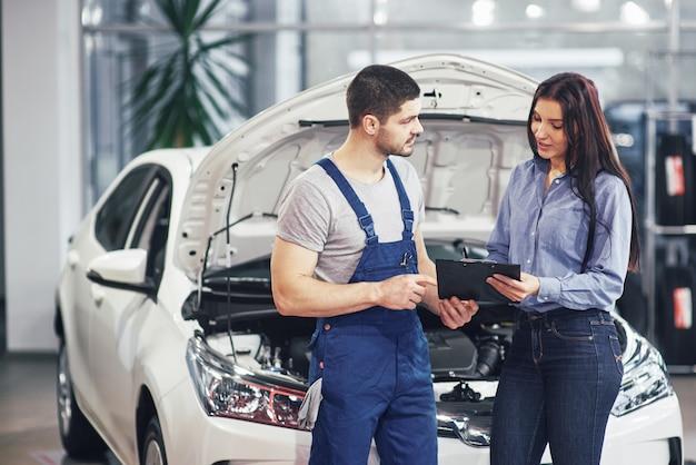 彼女の車に行われた修理を議論する男性メカニックと女性の顧客