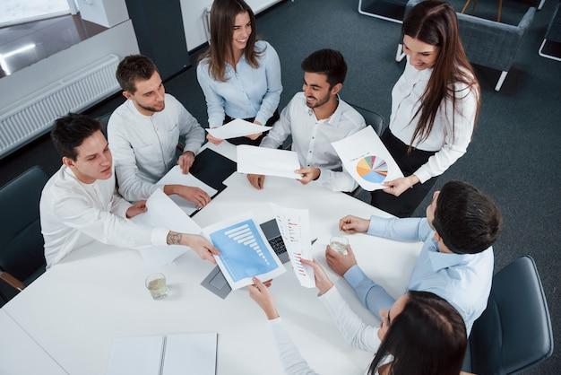 Такой молодой, но такой успешный. вид сверху офисных работников в классической одежде сидит возле стола, используя ноутбук и документы