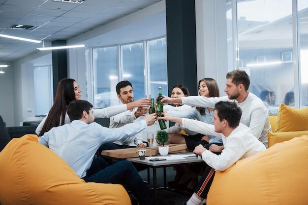 Празднование успешной сделки. молодые офисные работники сидят возле стола с алкоголем